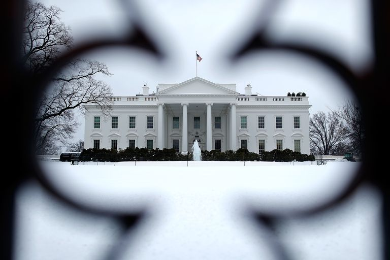 White House North Facade with pediment and columns Seen Through Iron Fence and snow-covered lawn