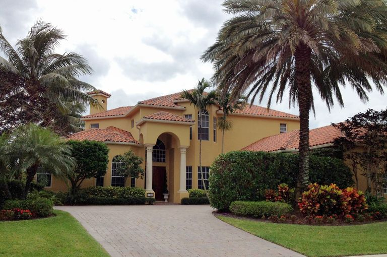 Light Browh Stucco House Red Tile Roof Arches And Columns Amidst Palm Trees