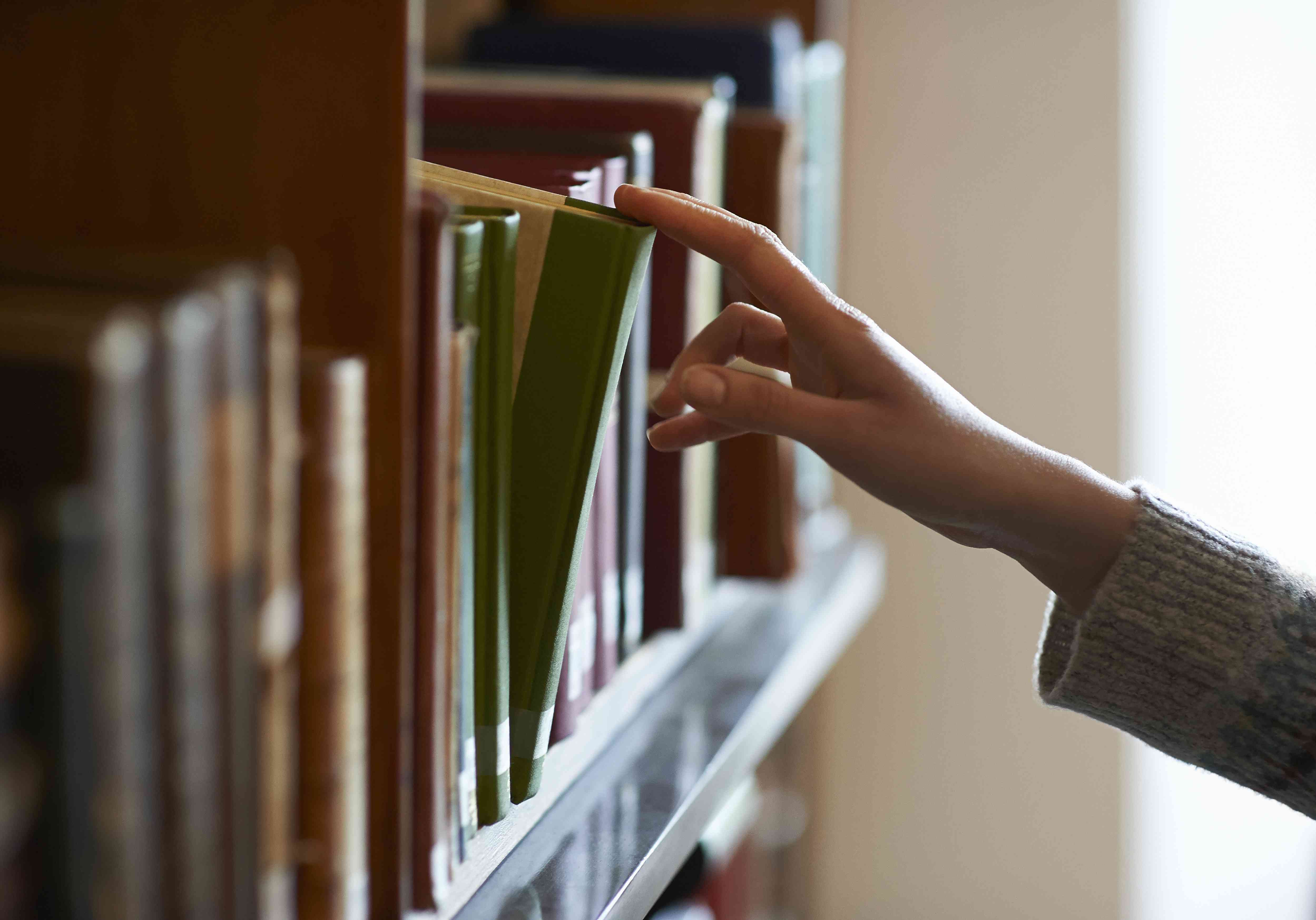 Hand taking old book from shelf in library.