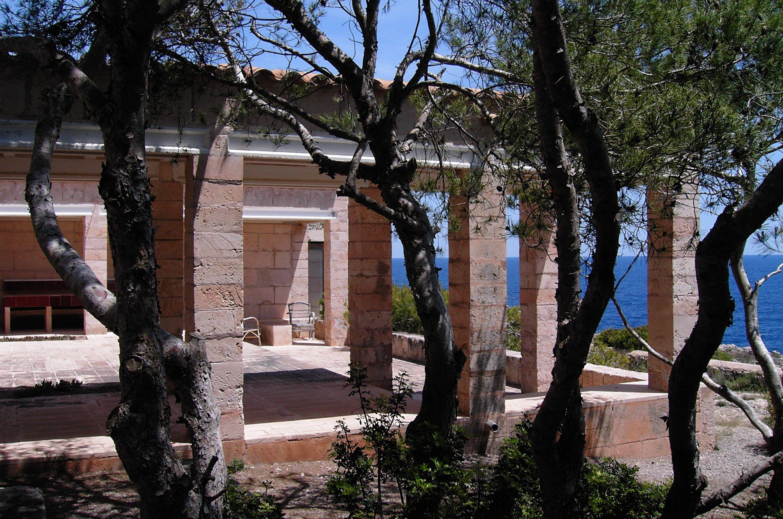 detalj av murstein søyler hvor med trestammer i en bolig plass åpen mot havet
