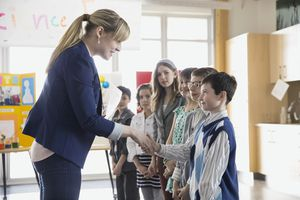 Elementary teacher handshaking with students at science fair