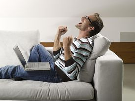 A man on his couch celebrates something on his laptop screen