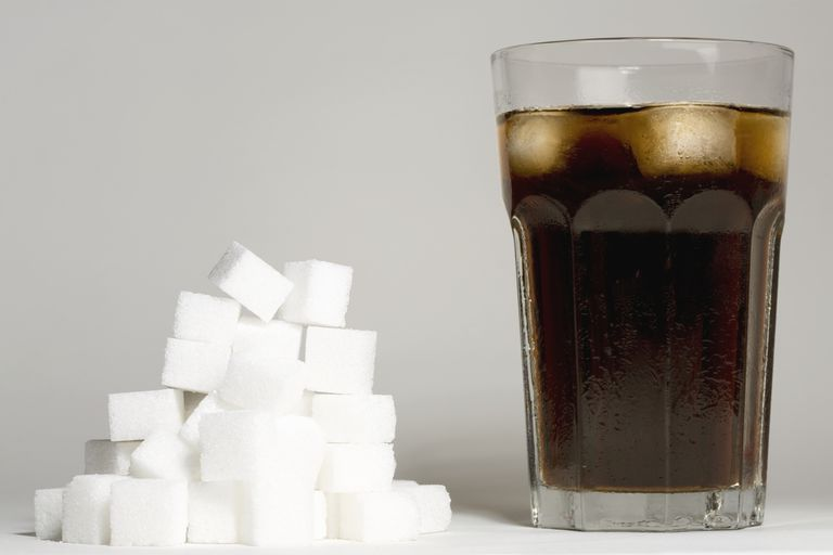 A glass of soda next to a pile of sugar cubes