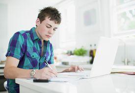 Teenage boy using laptop and doing homework