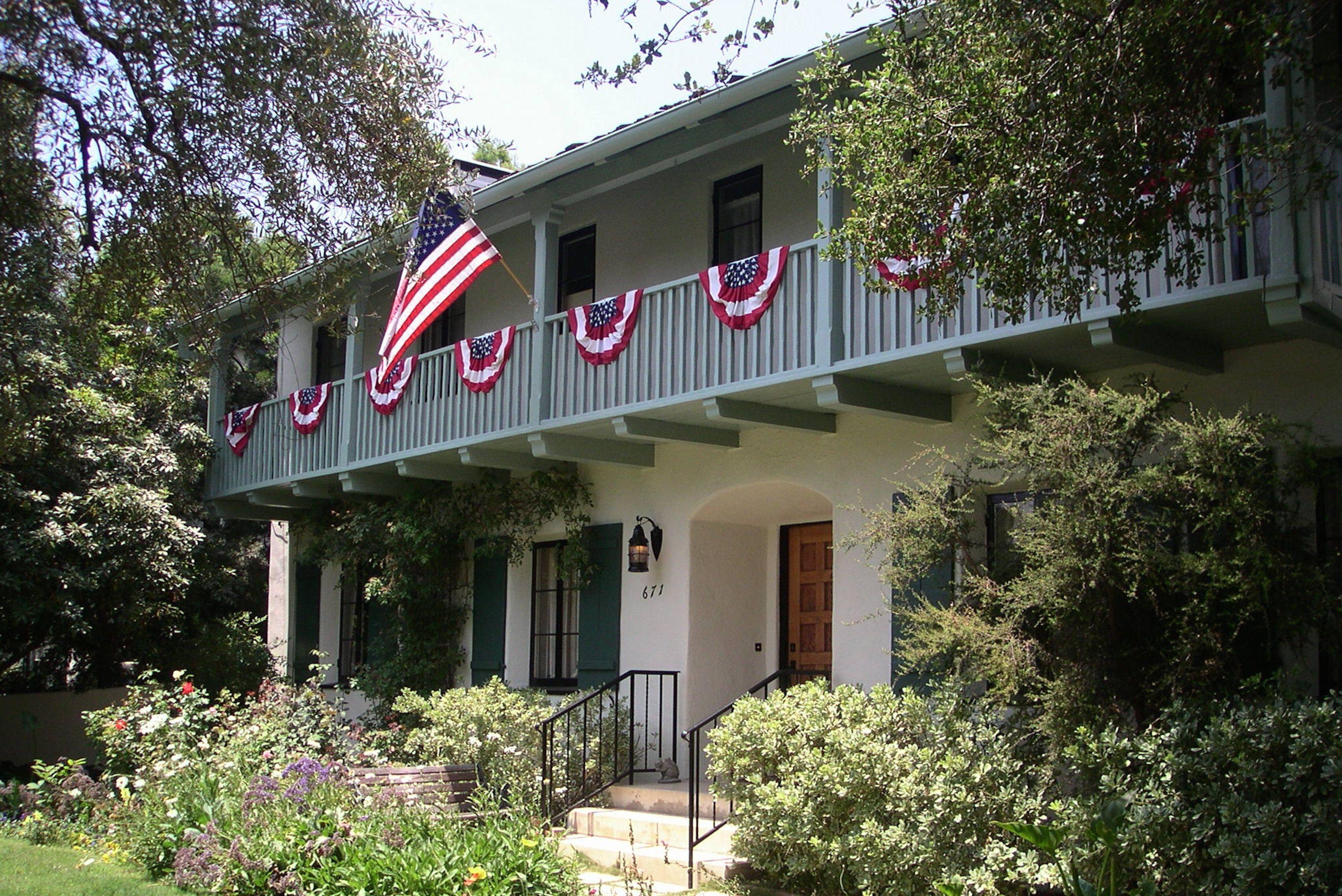 bannières drapeau américain pendent au deuxième étage porche de ce Monterey Colonial Revival