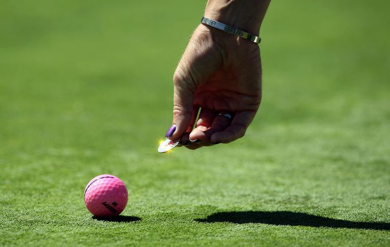 Golfer reaching down with coin to mark golf ball