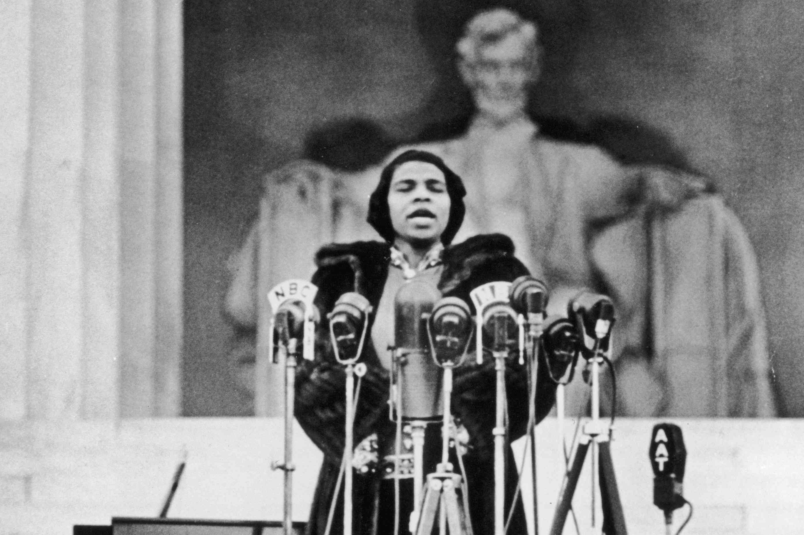 Marian Anderson standing in front of several microphones, closing her eyes, and singing with the Lincoln Statue in the background