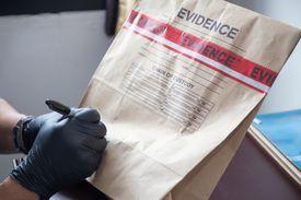 A gloved hand writing on an evidence bag.