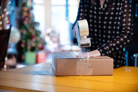 A woman sealing a box with tape in order to return it