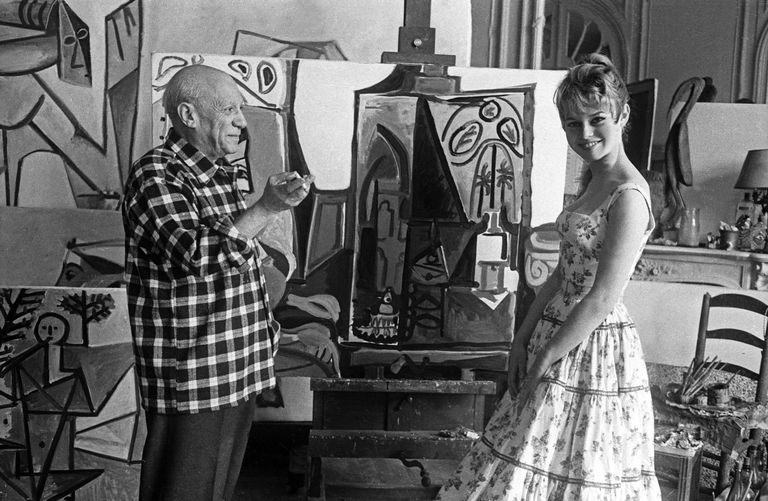Pablo Picasso stands in front of one of his paintings with Brigitte Bardot