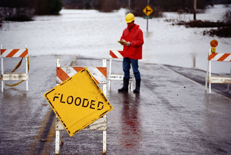 "Man in orange jacket standing next to flooded area and ""flooded"" sign"
