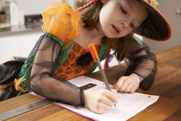A girl in a Halloween costume working on a math worksheet.