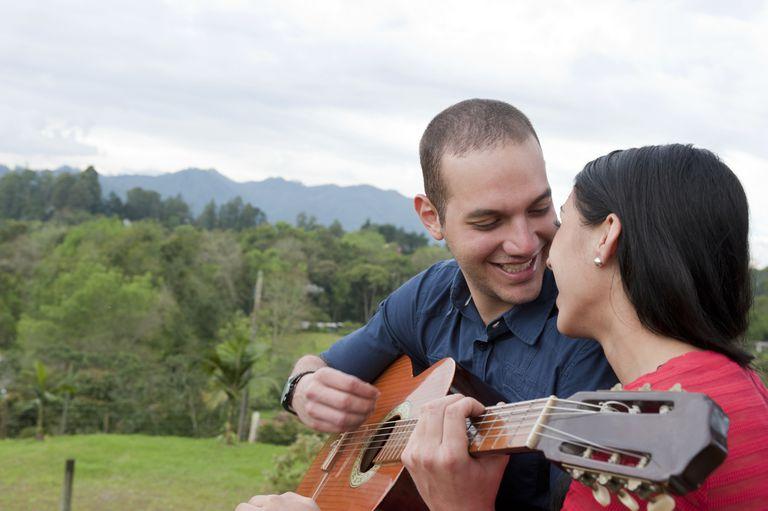 Hispanic man playing guitar for girlfriend