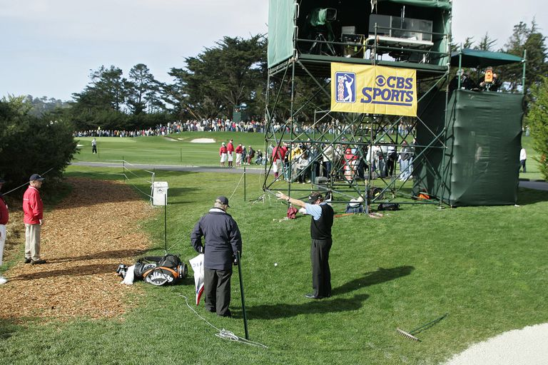 Phil Mickelson makes a drop to get out from behind the broadcast tower, a temporary immovable obstruction