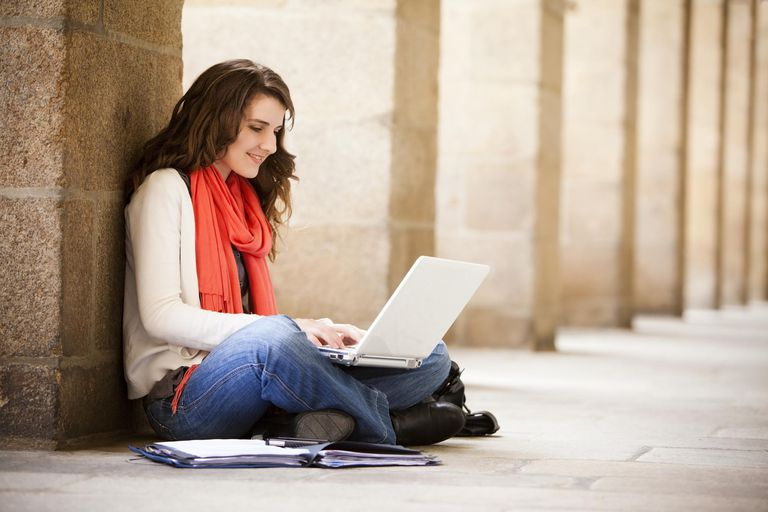 college woman sitting on ground with laptop