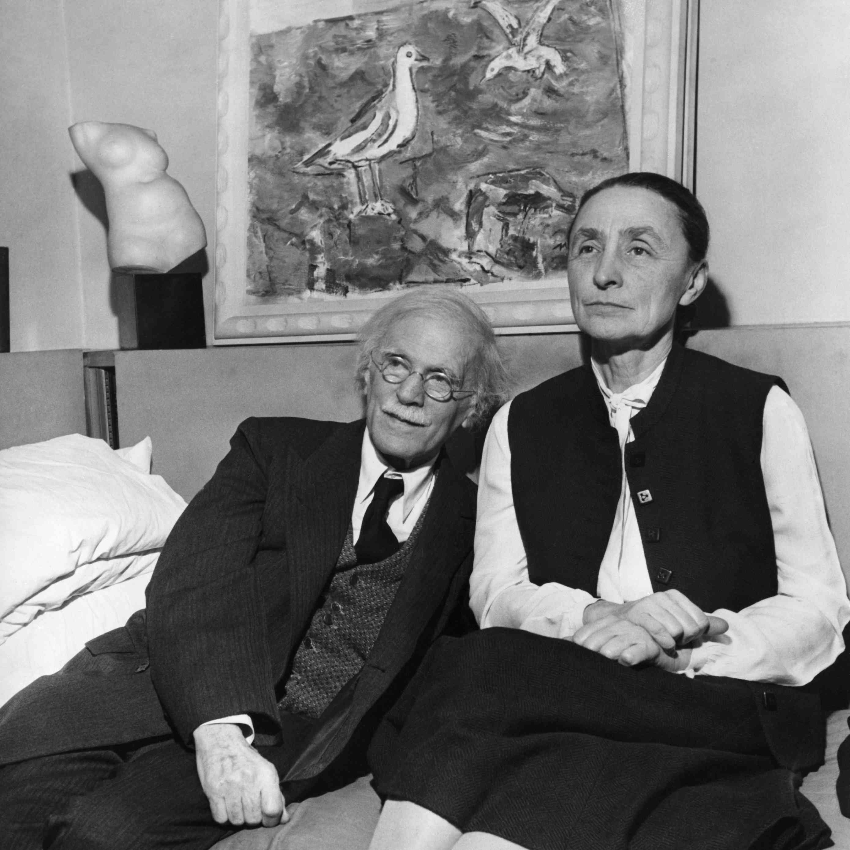 Alfred Stieglitz sits to the left of his wife Georgia O'Keeffe beneath a painting and sculpture