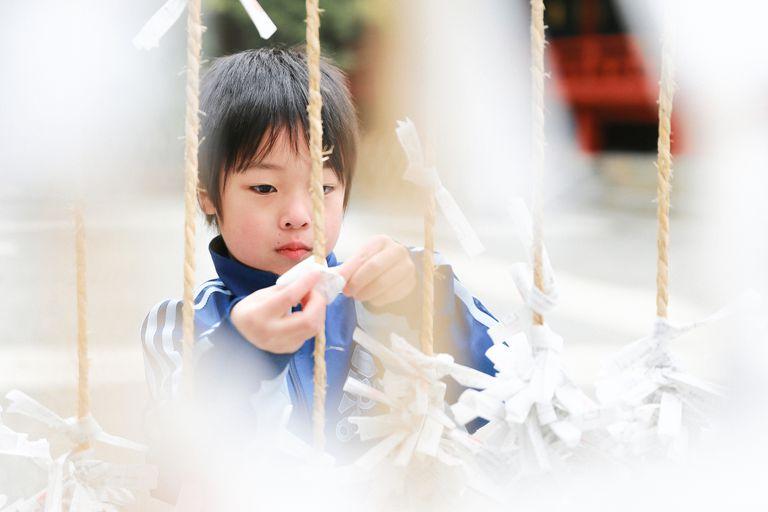 Child selecting an omikuji at a Shintō shrine.
