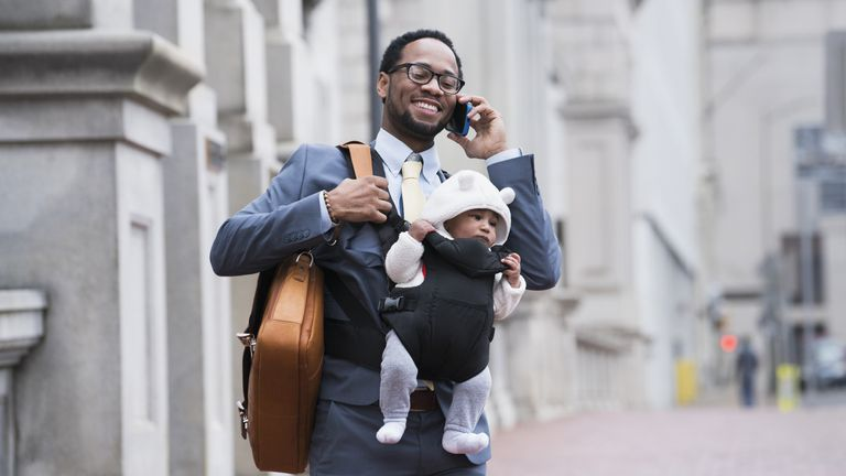 Black businessman with son in baby carrier talking on cell phone