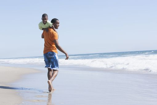Father carrying son in waves on beach