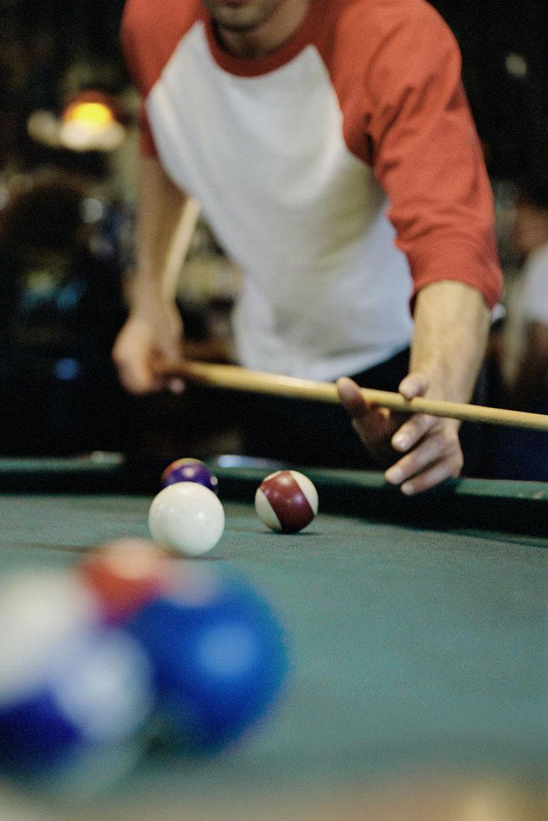 Man playing pool, mid section