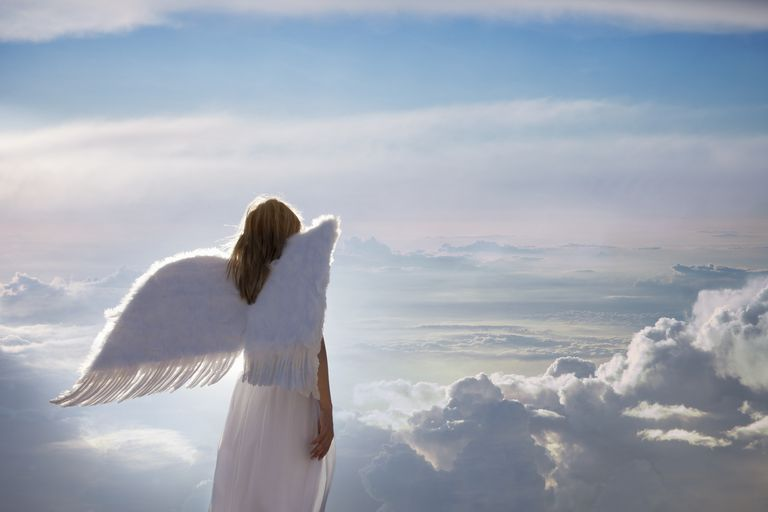 Woman with angel wings overlooking clouds.