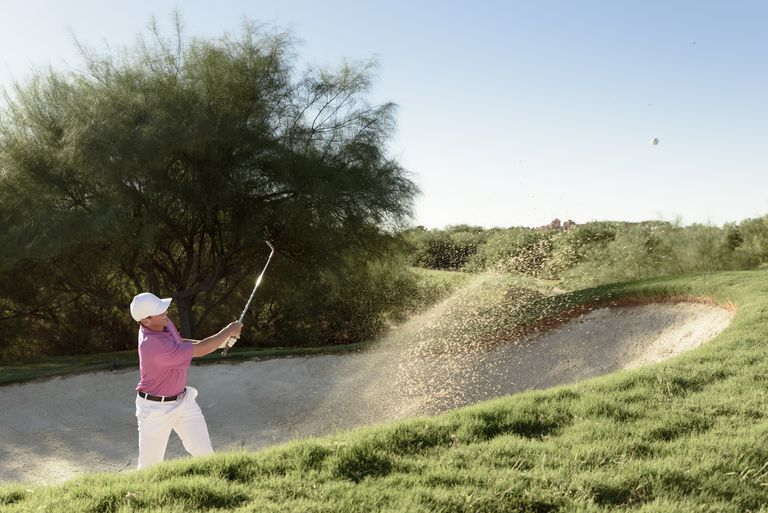 Golfer plays out of a bunker, which is covered in golf's Rule 12.