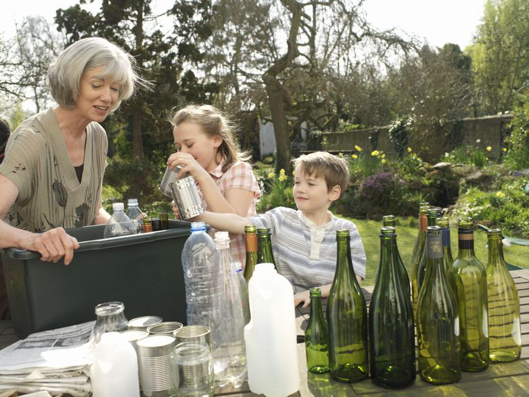 Grandmother and grandchildren sort bottles, plastic and paper for recycling.
