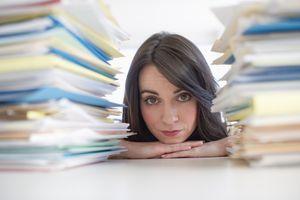 Mujer con montones de papeles para solicitar ajuste estatus