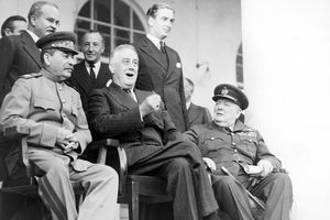 Black and white photo of Stalin, Roosevelt, and Churchill during the Tehran Conference.