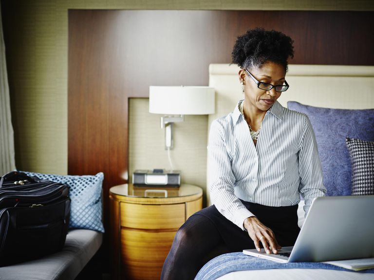 Businesswoman in hotel suite working on laptop.