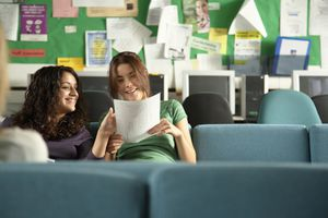 Two teenage girls in common room looking at paper