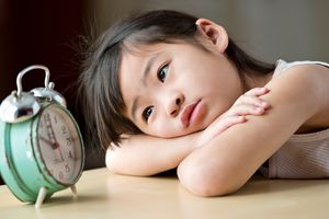 Portrait of a little girl sitting and staring at an old clock