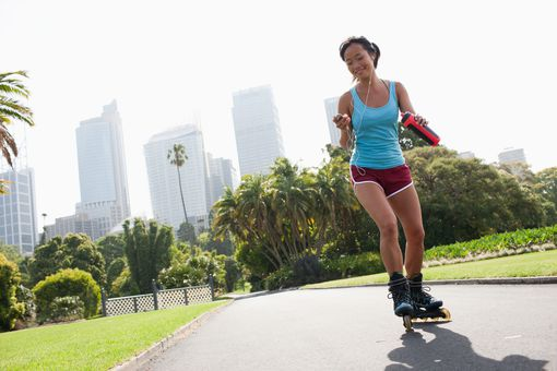 Woman inline skating through a city park
