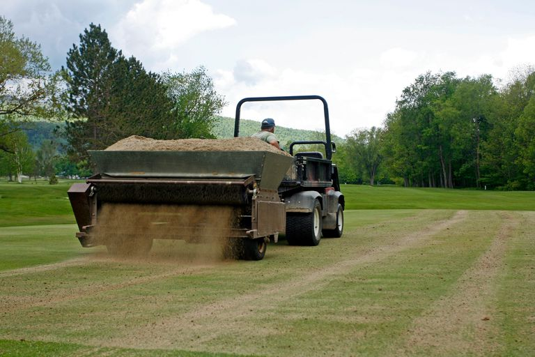 Topdressing a golf green following aeration