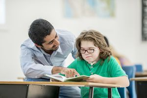 Teacher helping young student reading a book