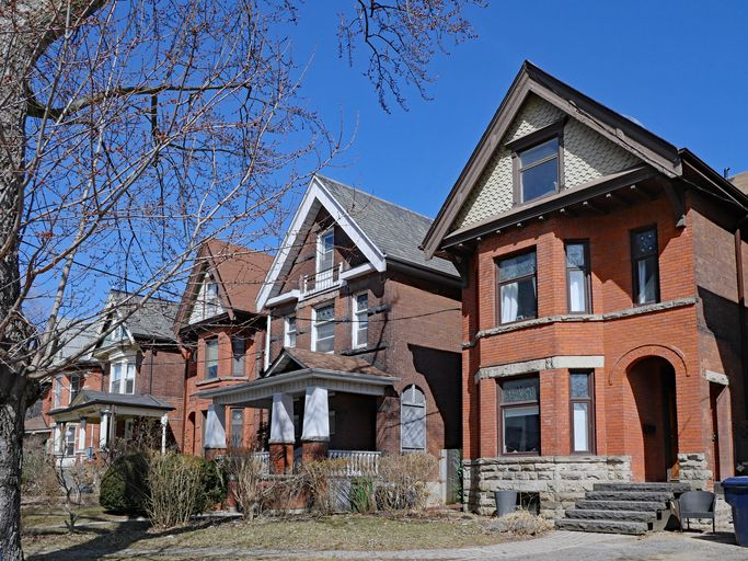 Row of large old Victorian style detached brick houses with gables.