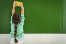 Girl cleaning chalk board