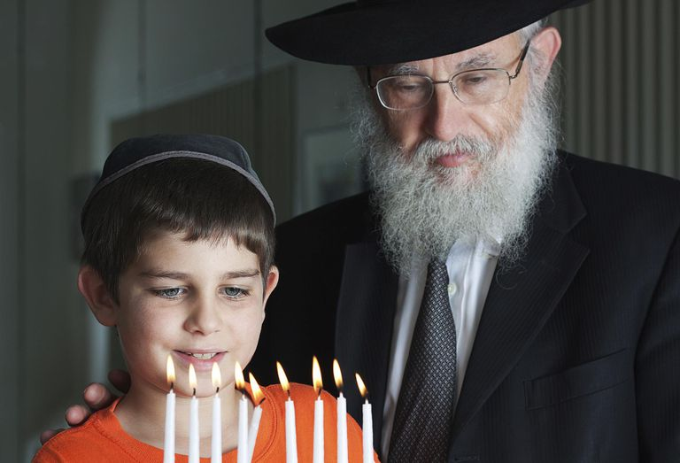 Two Jewish people celebrate Hanukkah by lighting the menorah