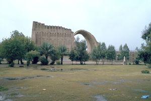 The Sassanian Arch behind a line of trees.