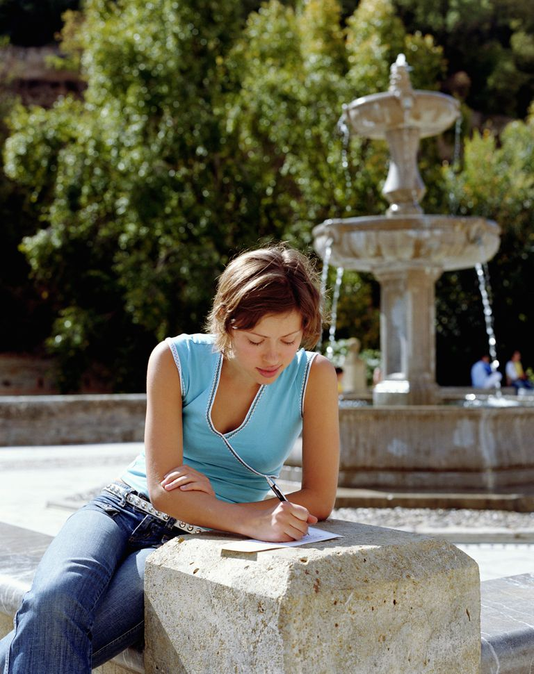 Woman writing a letter on college campus