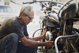 Older man examining his motorcycle