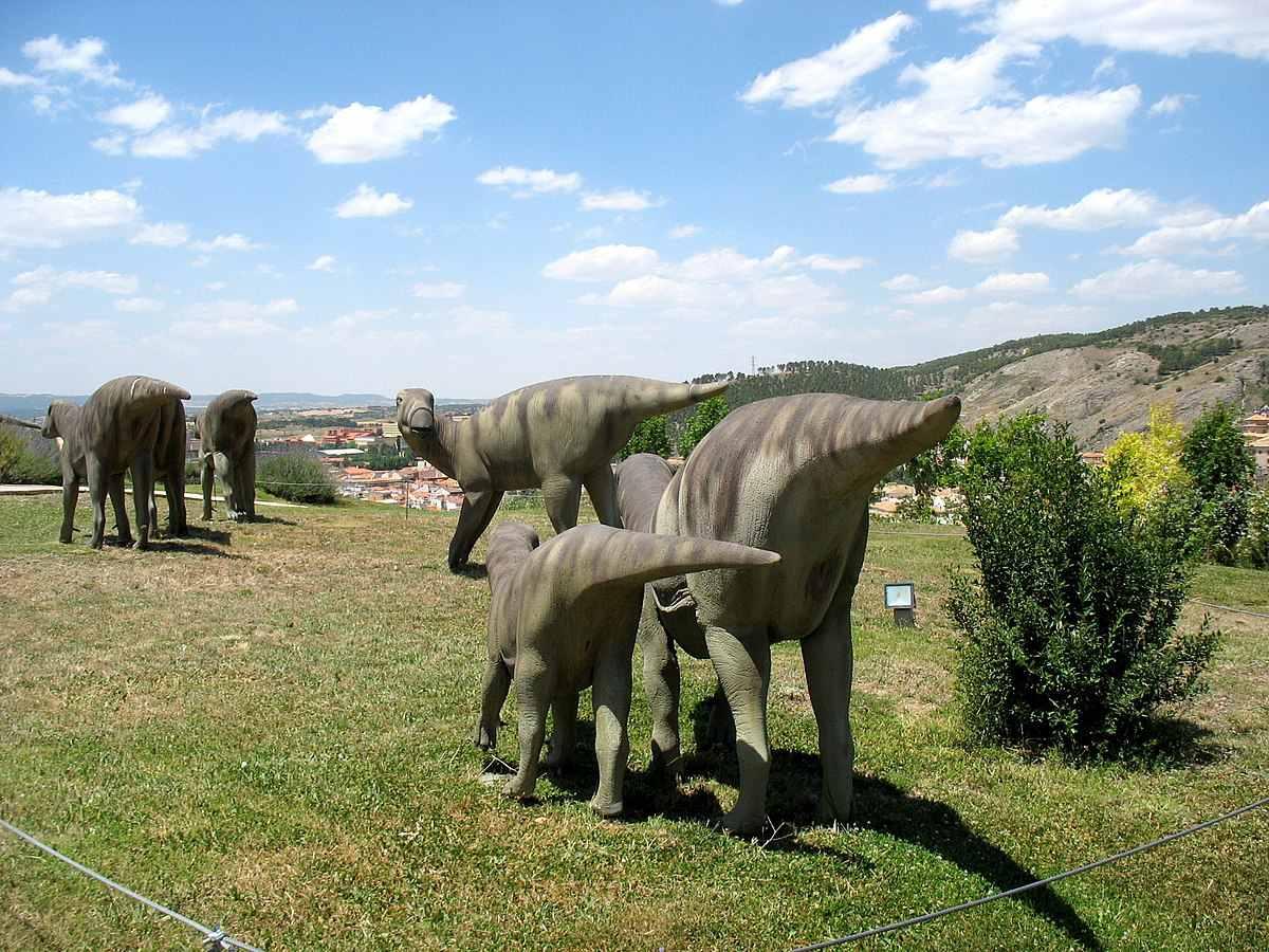 Exhibit of an Iguanodon herd walking on the grass.