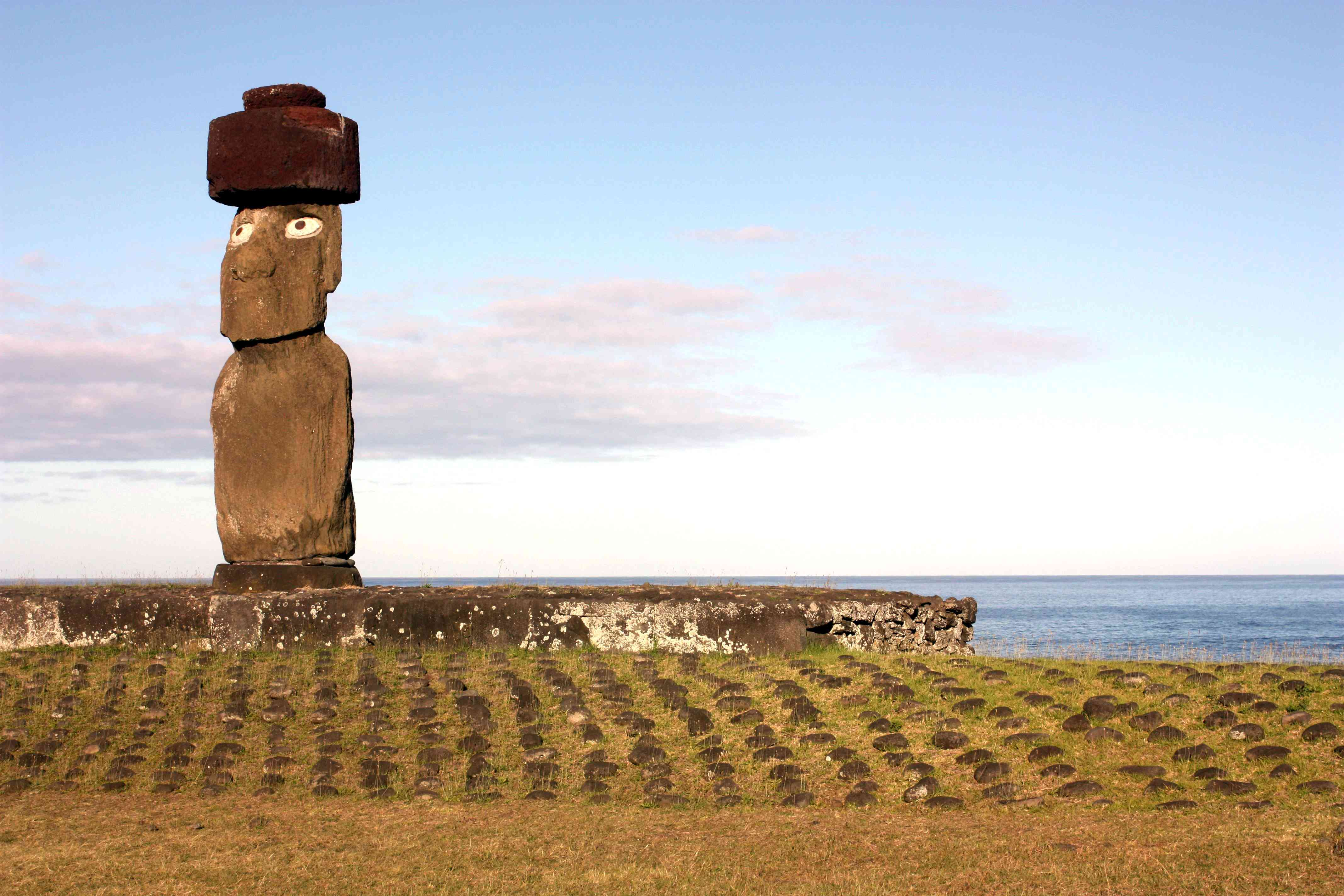 A moai with inset eyes and pukao headgear on an ahu platform with a ramp made of poro, round beach stones