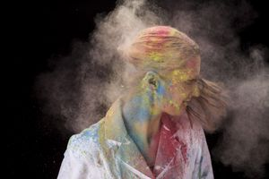Woman splattered with powder paint shaking hair
