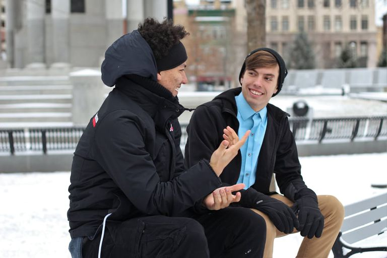 two men talking outdoors in cold weather