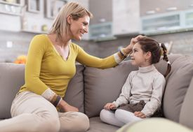 Happy mother talking to her daughter at home.