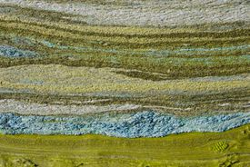 Green peat-silt with abstract horizontal lines.