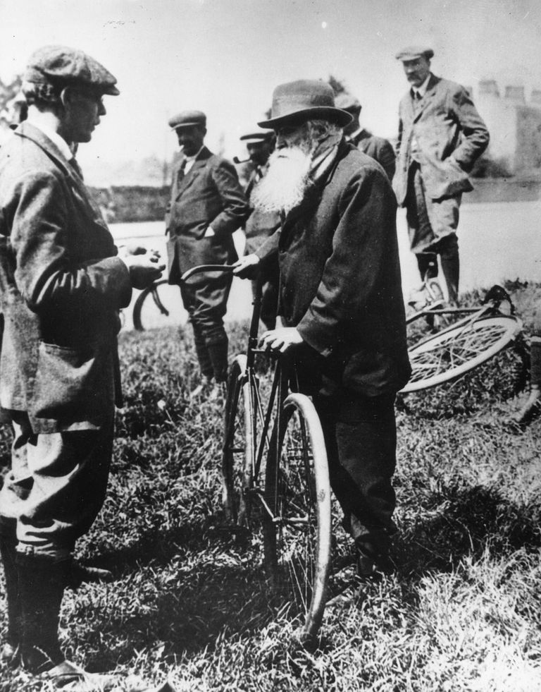 John Boyd Dunlop with the first bicycle to have pneumatic tires.