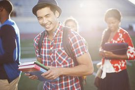 Student carrying books outdoors