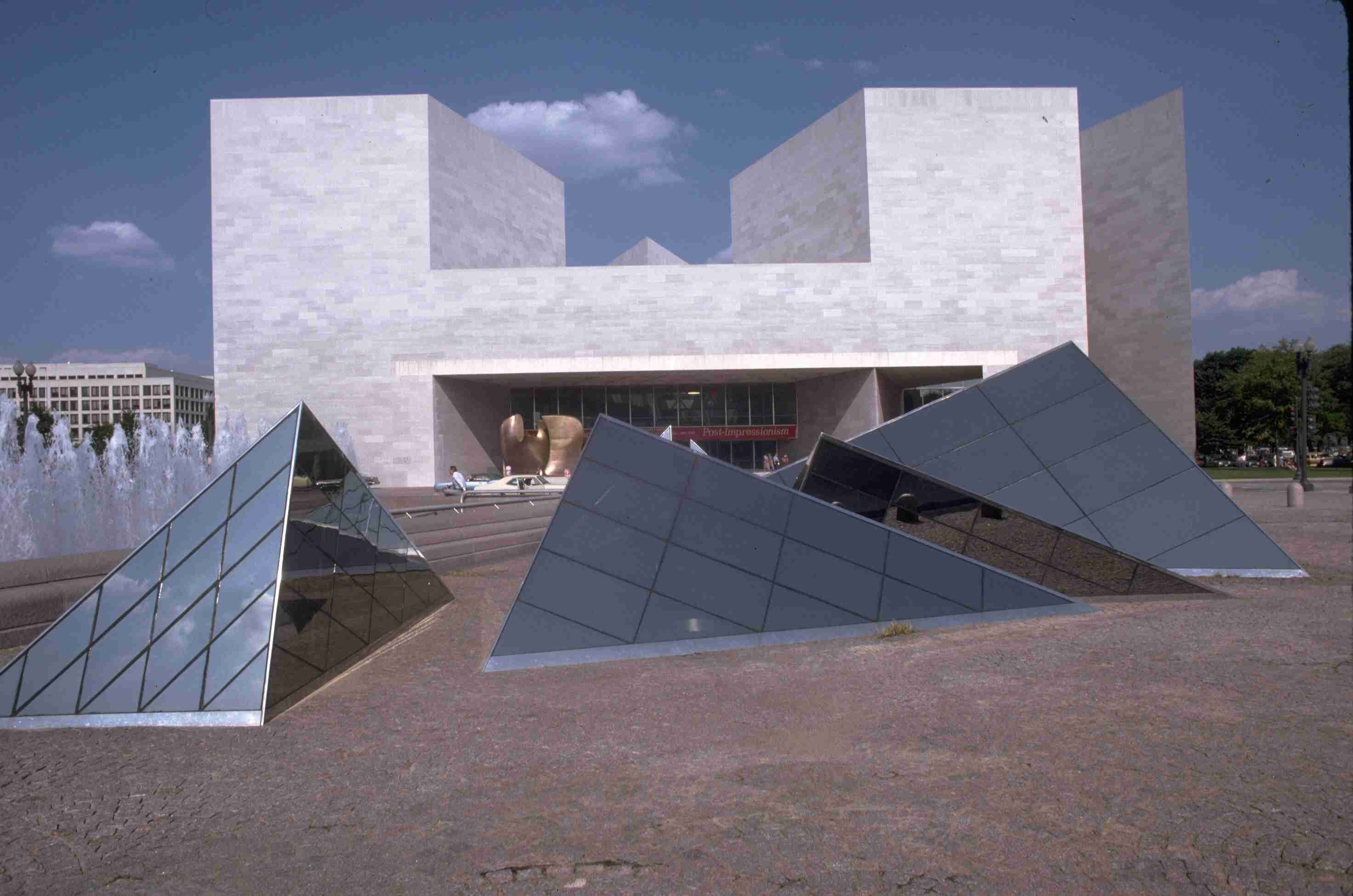 modern white stone building in background and glass pyramids on ground in foreground